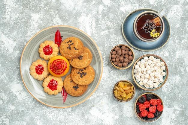 Bovenaanzicht heerlijke zandkoekjes met koekjes snoepjes en kopje thee op witte achtergrond thee suiker cookie zoete cake biscuit
