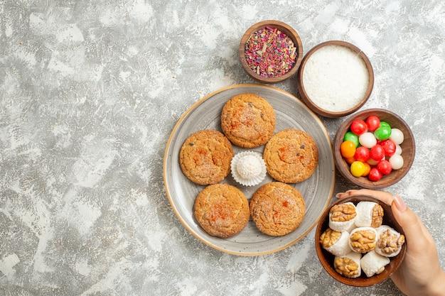 Bovenaanzicht heerlijke zandkoekjes met snoepjes op witte achtergrond