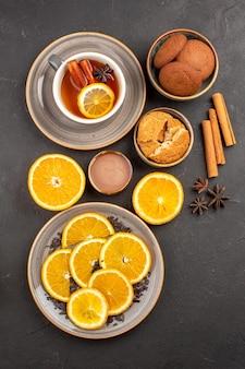 Bovenaanzicht heerlijke zandkoekjes met vers gesneden sinaasappels en kopje thee op donkere achtergrond, suikerkoekje, zoet koekjesfruit Gratis Foto