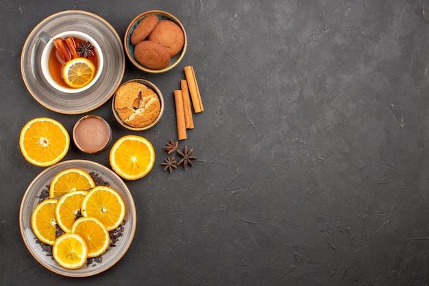 Bovenaanzicht heerlijke zandkoekjes met vers gesneden sinaasappels en kopje thee op donkere achtergrond, suikerkoekje, zoet koekjesfruit