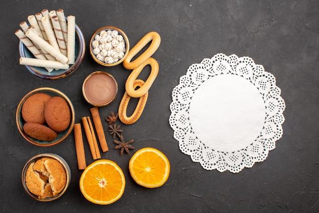 Bovenaanzicht heerlijke zandkoekjes met vers gesneden sinaasappels op donkere achtergrondkoekjes suiker fruit zoet citruskoekje