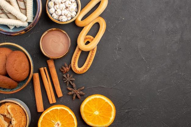 Bovenaanzicht heerlijke zandkoekjes met vers gesneden sinaasappels op donkere achtergrondkoekjes, suikerfruit, zoete citruskoekjes