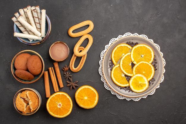 Bovenaanzicht heerlijke zandkoekjes met vers gesneden sinaasappels op donkere achtergrondkoekjes, zoete citrussuikerkoekjesfruit