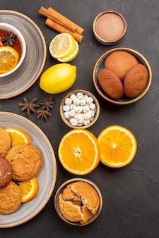 Bovenaanzicht heerlijke zandkoekjes met verse sinaasappels en kopje thee op donkere achtergrond fruitkoekje zoete koekje citrus