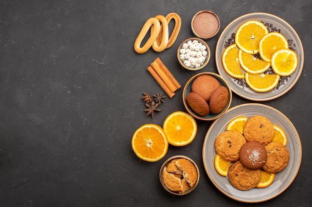 Bovenaanzicht heerlijke zandkoekjes met verse sinaasappels op donkere achtergrond fruitkoekje zoete koekje citrus