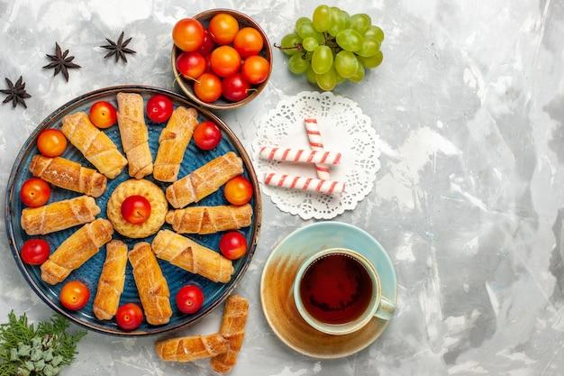 Bovenaanzicht heerlijke zoete bagels met zure pruimen en thee op lichtwit bureau
