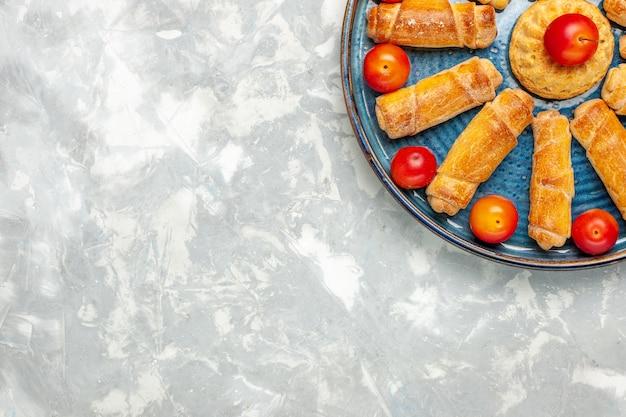 Bovenaanzicht heerlijke zoete bagels met zure pruimen op het lichte witte bureau