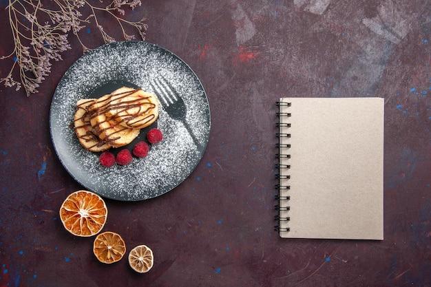 Bovenaanzicht heerlijke zoete broodjes gesneden cake voor een kopje thee op de donkere achtergrond roll biscuit zoete taart cake dessert
