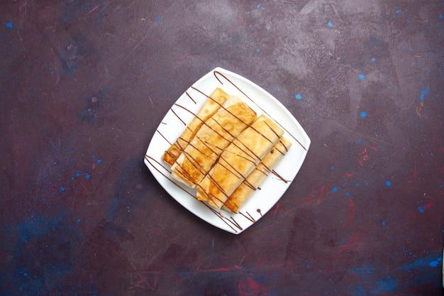 Bovenaanzicht heerlijke zoete gebakjes in plaat op de donkere ruimte