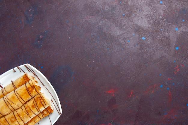 Bovenaanzicht heerlijke zoete gebakjes in plaat op donker bureau