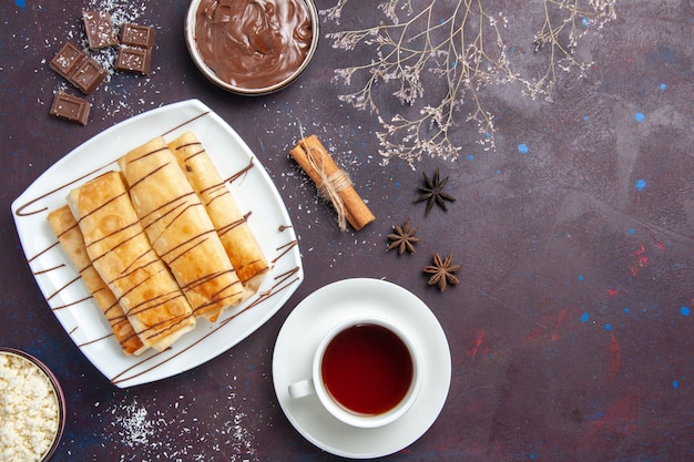 Bovenaanzicht heerlijke zoete gebakjes met chocolade en kopje thee op de donkere ruimte