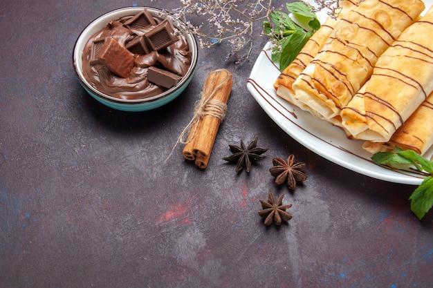 Bovenaanzicht heerlijke zoete gebakjes met chocolade op de donkere ruimte