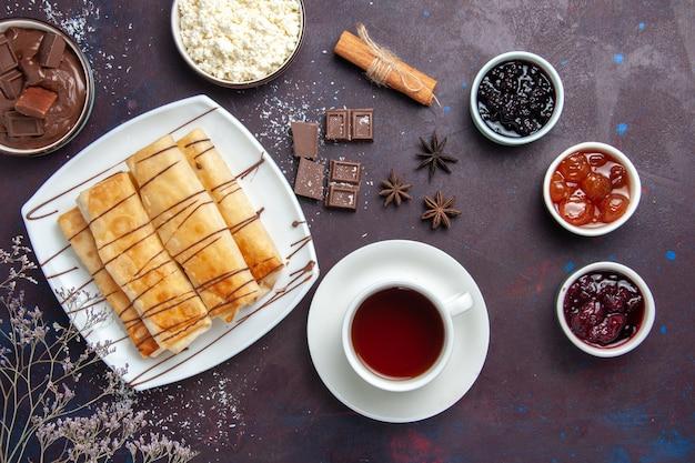 Bovenaanzicht heerlijke zoete gebakjes met chocoladejam en kopje thee op donkere ruimte
