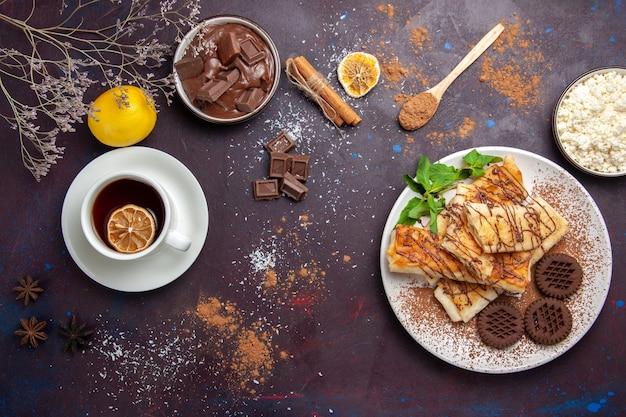 Bovenaanzicht heerlijke zoete gebakjes met chocoladekoekjes en kopje thee op donkere ruimte