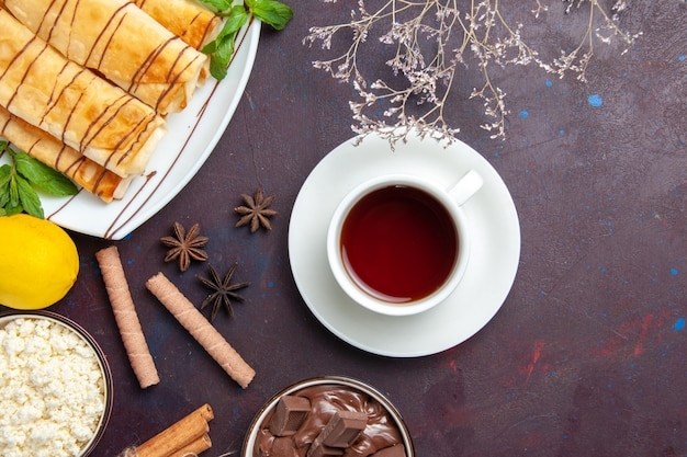Bovenaanzicht heerlijke zoete gebakjes met citroen en kopje thee op donkere ruimte