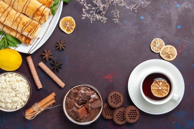 Bovenaanzicht heerlijke zoete gebakjes met koekjes en thee op de donkere ruimte