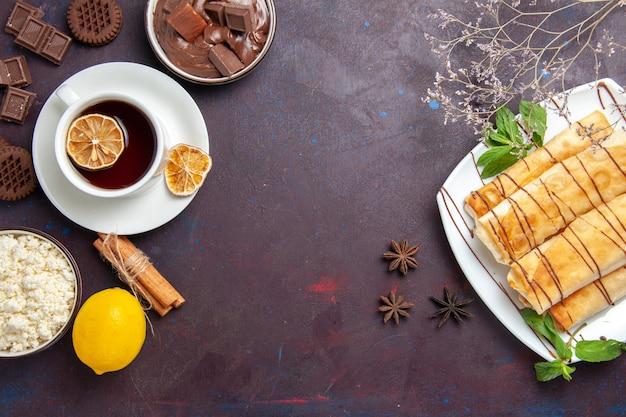 Bovenaanzicht heerlijke zoete gebakjes met kopje thee, chocolade en koekjes op de donkere ruimte