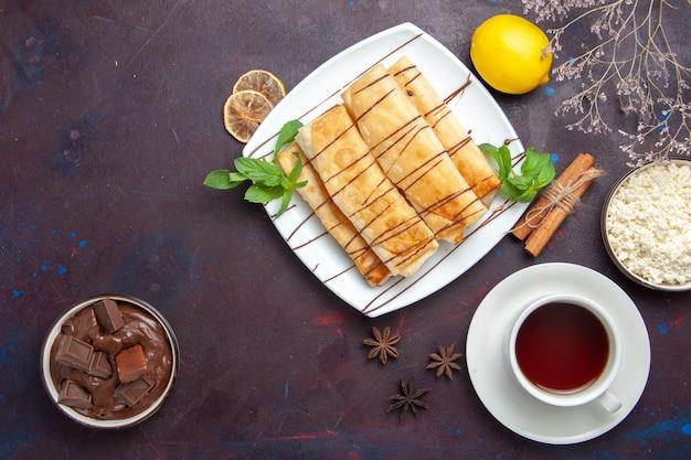 Bovenaanzicht heerlijke zoete gebakjes met kopje thee en chocolade op de donkere ruimte