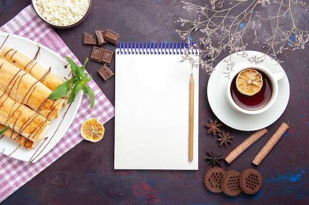 Bovenaanzicht heerlijke zoete gebakjes met kopje thee en koekjes op de donkere ruimte