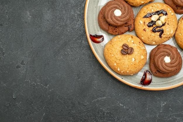 Bovenaanzicht heerlijke zoete koekjes lekkere snoepjes voor thee op grijs bureau