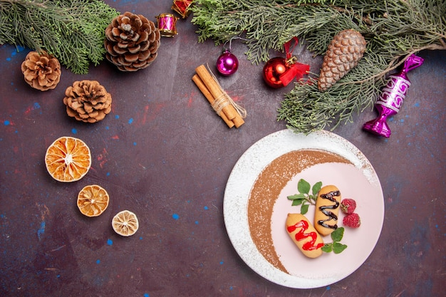 Bovenaanzicht heerlijke zoete koekjes met kerstspeelgoed op donkere achtergrond cookie zoete biscuit suiker kleur cake