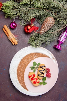 Bovenaanzicht heerlijke zoete koekjes met kerstspeelgoed op donkere achtergrond koekjes zoete koekjes suiker kleur cake color