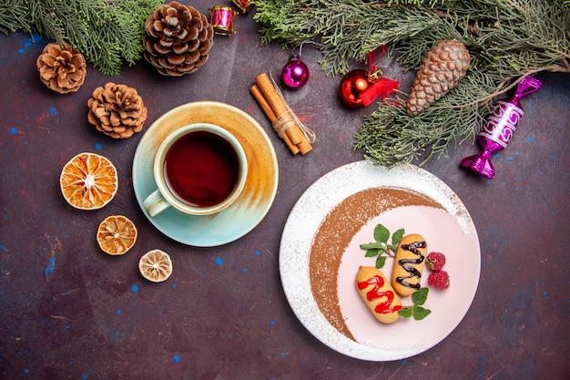 Bovenaanzicht heerlijke zoete koekjes met kopje thee op donkere achtergrond cookie zoete biscuit suiker kleur cake