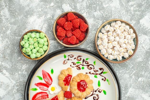 Bovenaanzicht heerlijke zoete koekjes met rode gelei en snoepjes op witte achtergrond zoete biscuit cake cookie-thee