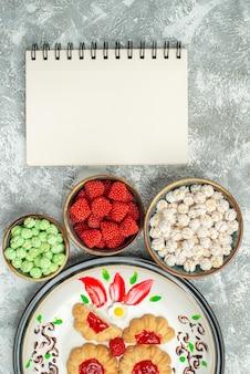 Bovenaanzicht heerlijke zoete koekjes met snoepjes op witte achtergrond cake zoete koekjes koekjes thee