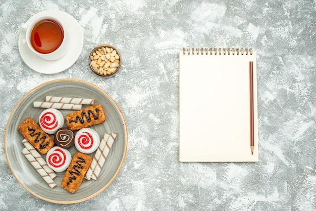 Bovenaanzicht heerlijke zoete koekjes met taarten en thee op witte ruimte