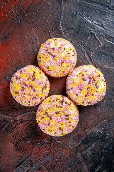 Bovenaanzicht heerlijke zoete koekjes op donkerrode achtergrond zoete horizontale taart biscuit suiker thee taarten