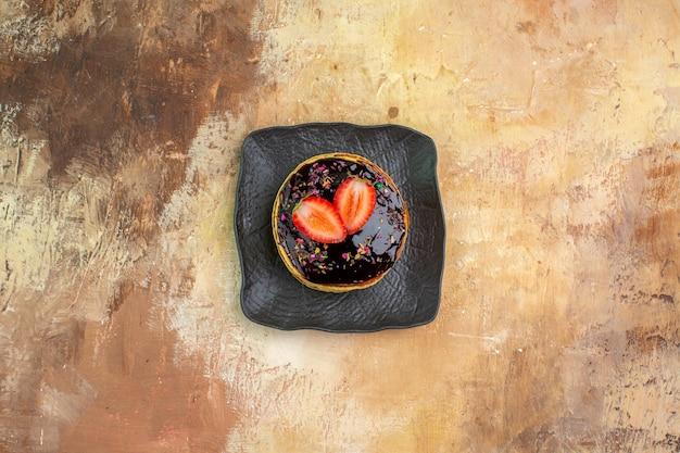 Bovenaanzicht heerlijke zoete pannenkoeken met choco glazuur op licht bureau
