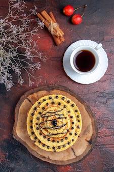 Bovenaanzicht heerlijke zoete pannenkoeken met kopje thee op donkere ondergrond