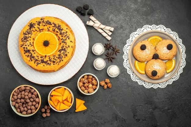 Bovenaanzicht heerlijke zoete taart met stukjes sinaasappel en koekjes op donkergrijs oppervlak fruittaart cake deeg biscuit