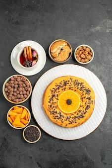Bovenaanzicht heerlijke zoete taart met stukjes sinaasappel en kopje thee op donkere oppervlakte koekjes taart biscuit dessert thee cake
