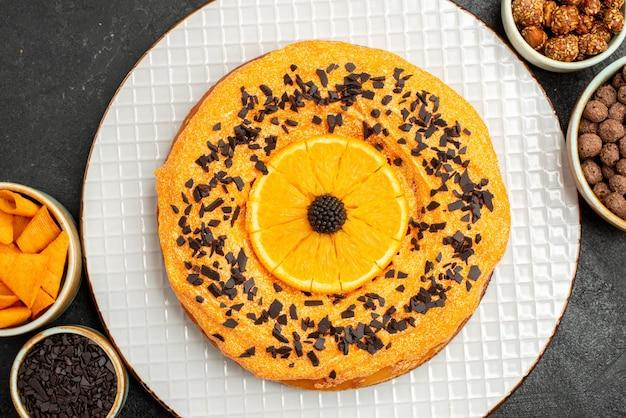 Bovenaanzicht heerlijke zoete taart met stukjes sinaasappel op donkere oppervlakte taart biscuit cake dessert cookie thee