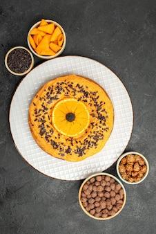 Bovenaanzicht heerlijke zoete taart met stukjes sinaasappel op donkere oppervlakte taart biscuit cake dessert thee cookie