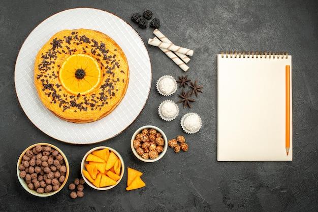 Bovenaanzicht heerlijke zoete taart met stukjes sinaasappel op donkergrijs oppervlak deeg fruittaart cake biscuit