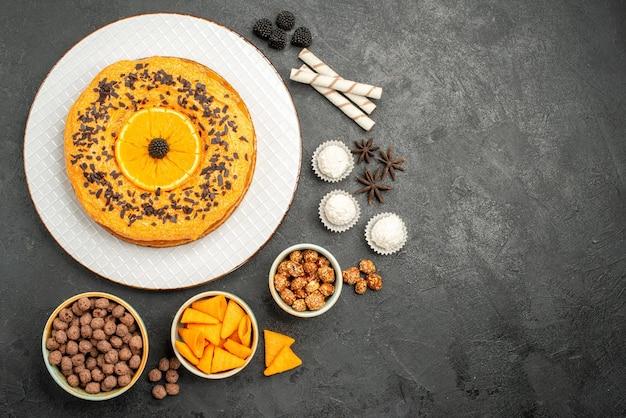 Bovenaanzicht heerlijke zoete taart met stukjes sinaasappel op donkergrijs oppervlak fruittaart cake deeg biscuit