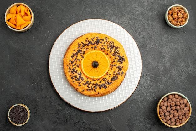 Bovenaanzicht heerlijke zoete taart met stukjes sinaasappel op donkergrijs oppervlak taart biscuit taart dessert thee koekje