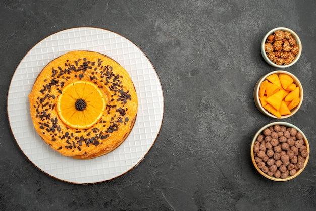 Bovenaanzicht heerlijke zoete taart met stukjes sinaasappel op donkergrijze oppervlakte taart taart dessert thee koekje