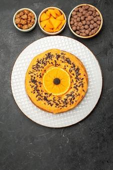 Bovenaanzicht heerlijke zoete taart met stukjes sinaasappel op donkergrijze oppervlakte taart taart dessert thee koekjes