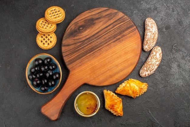 Bovenaanzicht heerlijke zoete taarten met olijven en koekjes op donkere ondergrond zoete taart