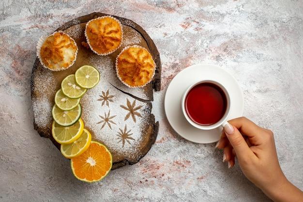 Bovenaanzicht heerlijke zoete taarten met schijfjes citroen en kopje thee op wit bureau