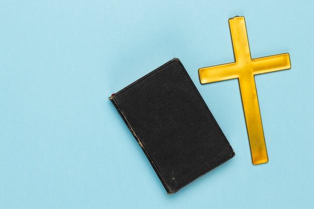 Bovenaanzicht heilig kruis en boek op tafel