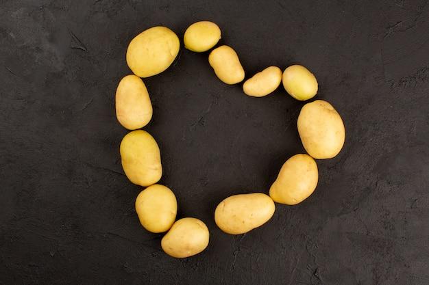 Bovenaanzicht hele aardappelen geschild op de donkere achtergrond