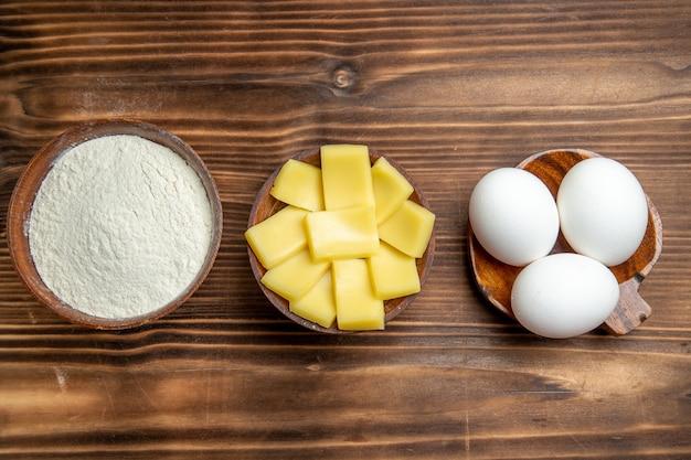 Bovenaanzicht hele rauwe eieren met bloem en kaas op de bruine tafel eieren deeg meel stof producten
