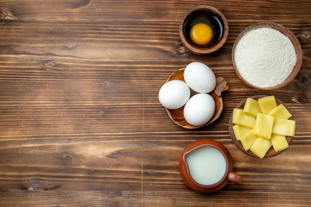 Bovenaanzicht hele rauwe eieren met bloem, melk en kaas op bruin tafeleieren deeg bloemstof product