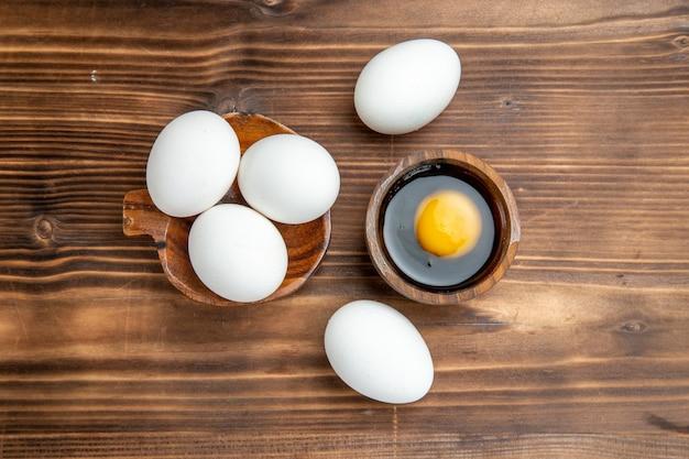 Bovenaanzicht hele rauwe eieren op bruin houten oppervlak maaltijd eten ontbijt houten ei
