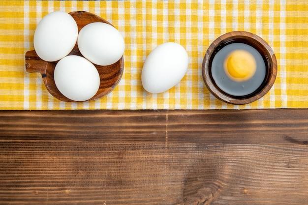 Bovenaanzicht hele rauwe eieren op bruin houten tafel eten ontbijt houten ei
